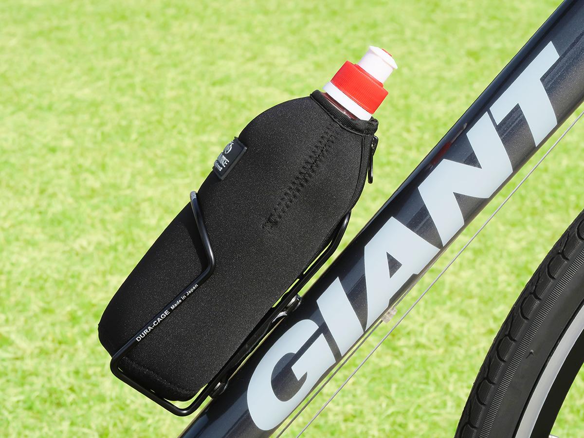 「POTABIKEペットボトルカバー」と「TNIの飲み口キャップ」を装着したペットボトルが自転車のボトルケージに収納されている写真