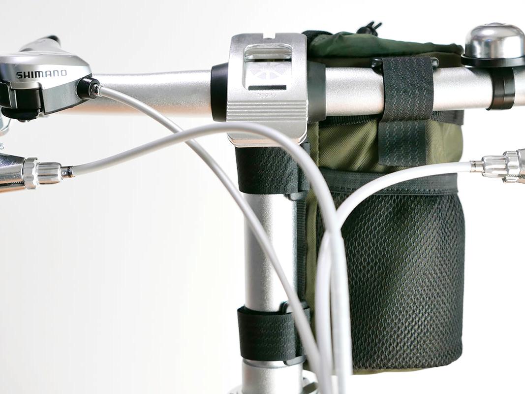 折り畳み自転車のT型ハンドルに3箇所のベルトが固定されている写真